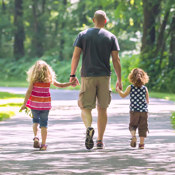Photo of a father walking with two children