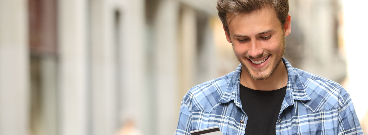Photo of young man holding a credit card