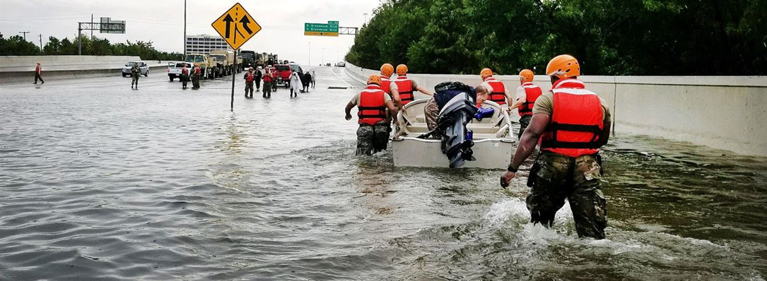 photo of hurricane relief workers on a flooded highway