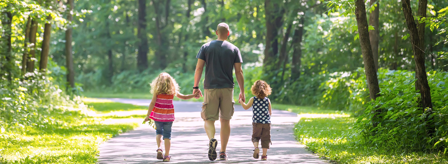 Photo of a father walking with two children.
