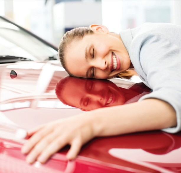 Photo of a woman hugging the hood of her shiny red car