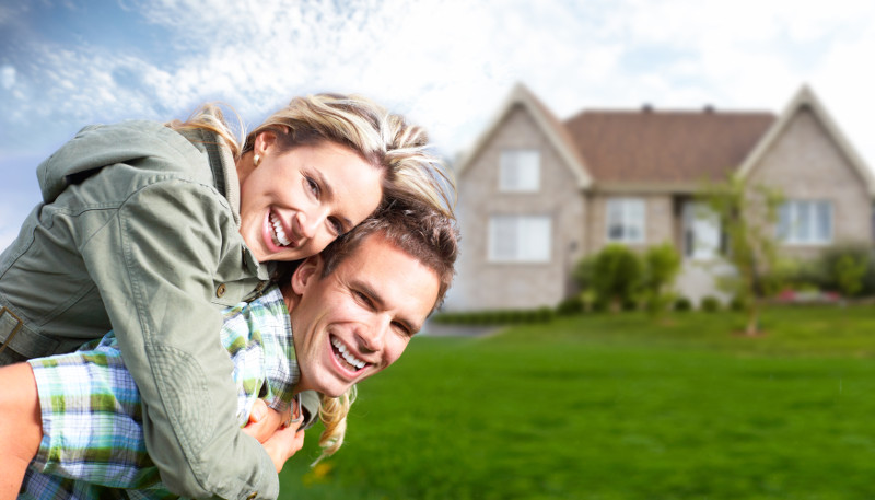 young couple in front of their new house.