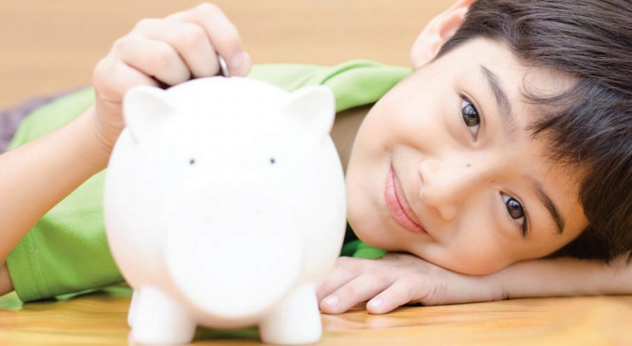 A boy putting a coin in a piggy bank.