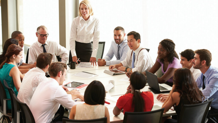 A diverse group of adults surrounding a boardroom table
