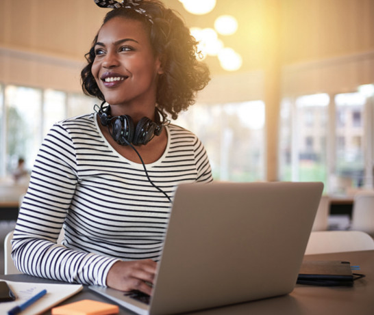 A young African American woman with a striped shirt and headphones sitting at a laptop.